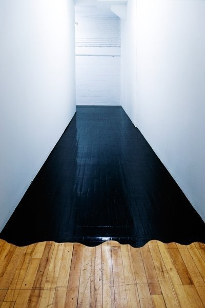 A hallway's transition is created with some high gloss black paint. via Apartment Therapy