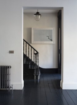 A solid black floor adds warmth to a home with white walls. via Apartment Therapy